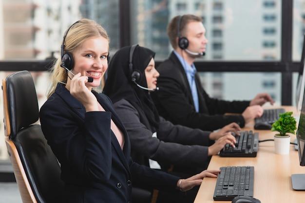 Operador de suporte sorridente com colegas em fones de ouvido trabalhando no escritório Foto Premium