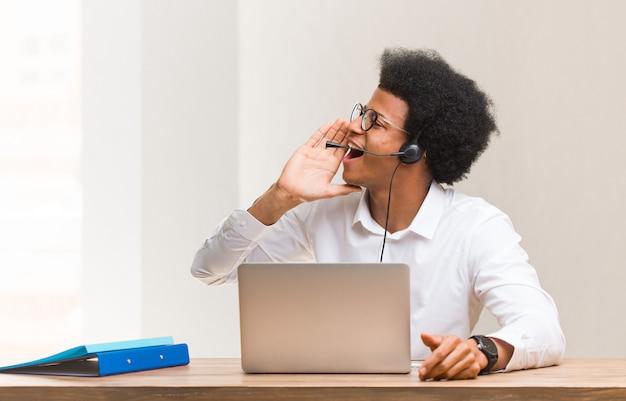 Operador de telemarketing jovem negro sussurrando fofoca Foto Premium