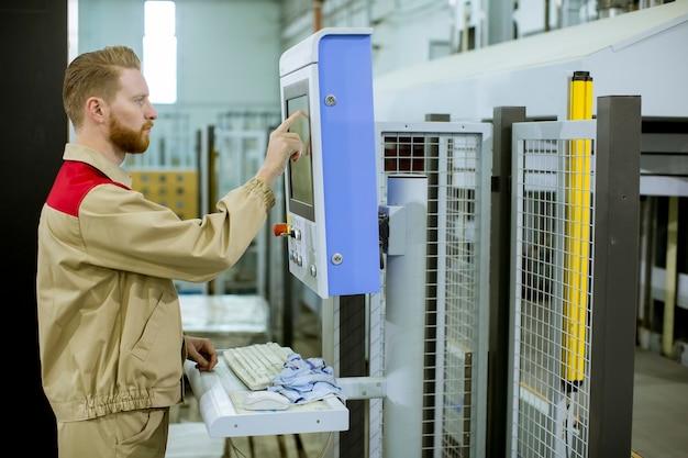Operador masculino pressiona o botão no painel de controle nos dispositivos de controle na instalação de produção de móveis Foto Premium