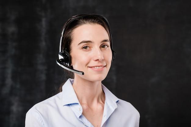 Operadora linda jovem morena com fone de ouvido falando com clientes durante o trabalho na frente da câmera contra um fundo preto Foto Premium