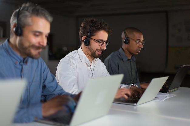 Operadores de centro de chamada alegre durante o processo de trabalho Foto gratuita