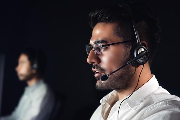 Operadores de serviço ao cliente asiático masculino trabalhando turno da noite no call center Foto Premium