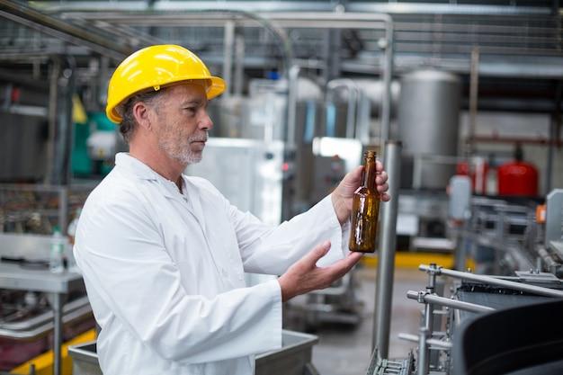 Operário examinando uma garrafa na fábrica Foto Premium