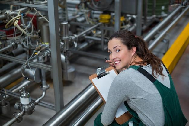 Operário feminino, mantendo o registro na área de transferência na fábrica Foto Premium