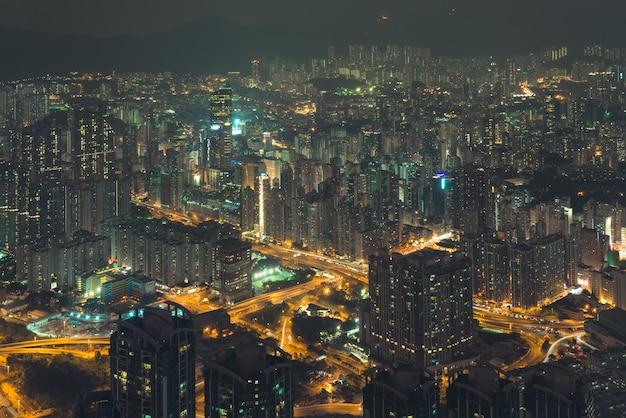 Opinião da cidade da noite de uma altura aos edifícios nas luzes e nas estradas da cidade. hong kong. Foto Premium