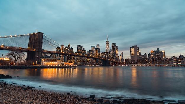 Opinião da noite da arquitectura da cidade da ponte de brooklyn e das construções em manhattan new york city, estados unidos. Foto Premium