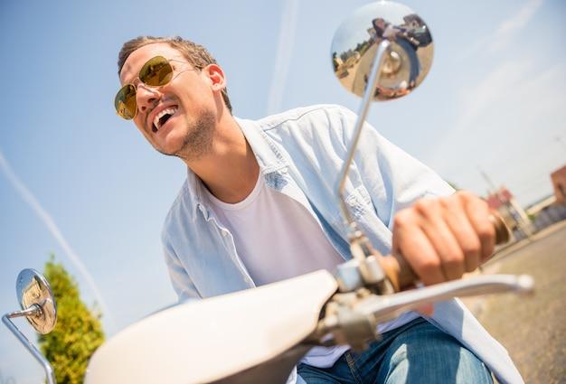 Opinião de baixo ângulo o homem novo considerável nos óculos de sol. Foto Premium