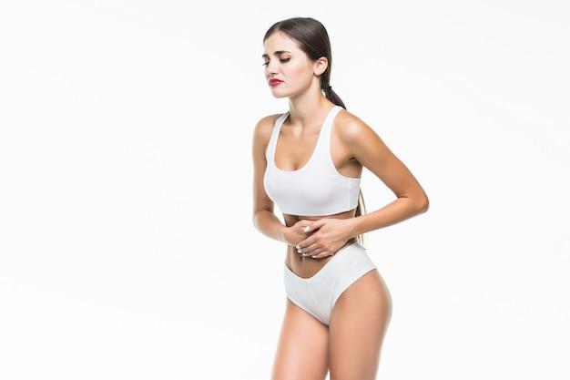 Opinião do close up uma jovem mulher com dor de estômago ou digestão ou ciclo do período na parede branca. Foto gratuita