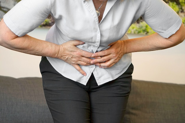 Opinião do close up uma mulher idosa que tem a dor de estômago dolorosa em casa. gastrite crônica. Foto Premium