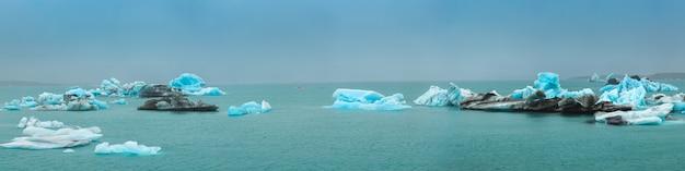 Opinião do panorama dos icebergs que flutuam na lagoa de jokulsarlon perto da costa do sul de islândia Foto Premium