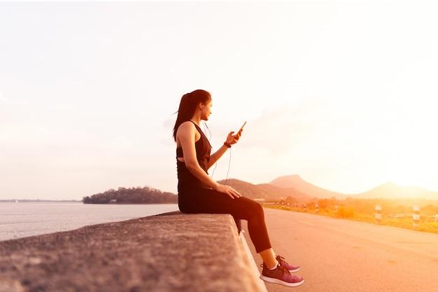 Opinião lateral a mulher do esporte com os fones de ouvido que sentam-se na parede após a corrida da tarde. Foto Premium