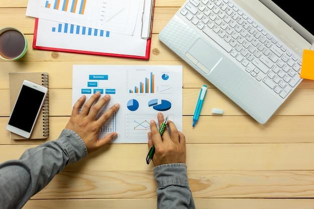 Opinião superior pessoa comercial discutindo gráficos e gráficos na mesa do escritório. Foto Premium