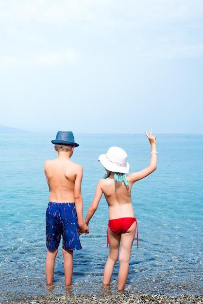 Opinião traseira a menina e o menino que guardam as mãos no beira-mar. Foto Premium
