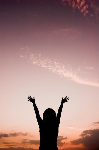 Opinião traseira a mulher com as mãos levantadas olhando para o céu Foto gratuita