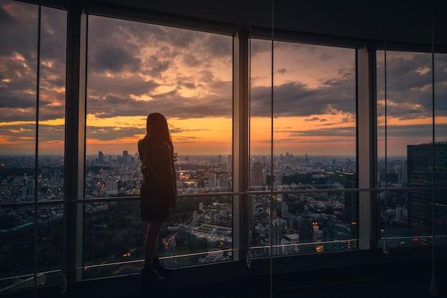 Opinião traseira a mulher do viajante que olha a skyline do tóquio e a vista dos arranha-céus na plataforma de observação no por do sol em japão. Foto Premium