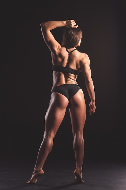 Opinião traseira a mulher muscular forte bonita Foto Premium