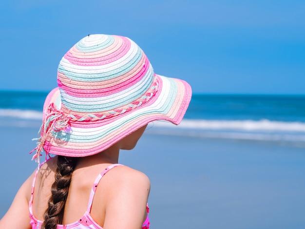 Opinião traseira uma menina adolescente que aprecia a vista na praia tropical. Foto Premium