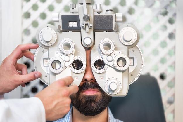 Optometrista fazendo testes de visão para o paciente do sexo masculino na clínica Foto Premium