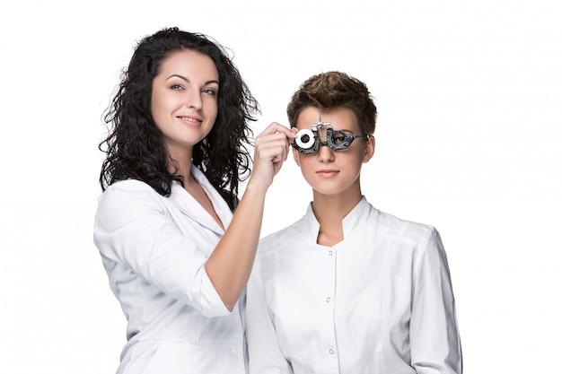 Optometrista segurando um olho teste óculos e dando ao exame de mulher jovem Foto gratuita