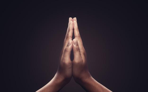 Orando com as mãos com fé na religião e crença em deus em fundo escuro Foto Premium
