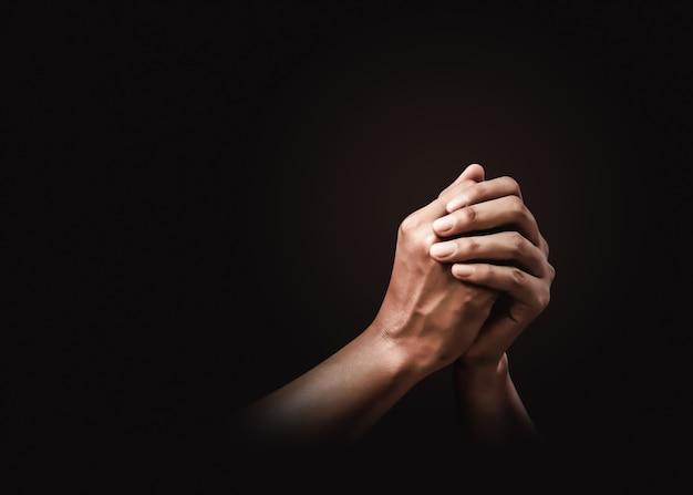 Orando mãos com fé na religião e crença em deus no escuro. poder da esperança ou amor e devoção. Foto Premium