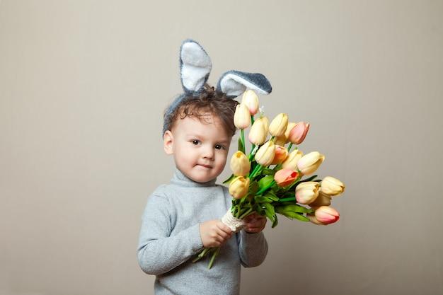 Orelhas de coelho bebê boyin com buquê de tulipas cor de rosa Foto Premium