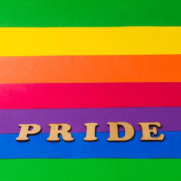 Orgulho palavra de madeira na bandeira colorida de lgbt Foto gratuita