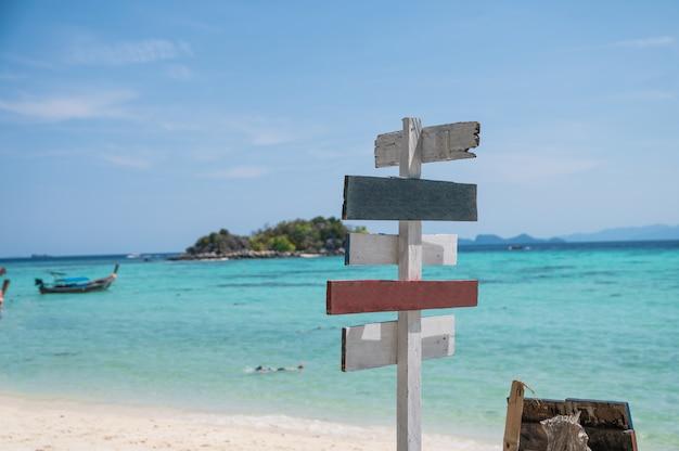 Orientação de flechas de madeira na praia branca com mar tropical Foto Premium