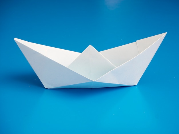 Origami de conceito de negócio papel de barco branco mínimo sobre fundo azul Foto Premium