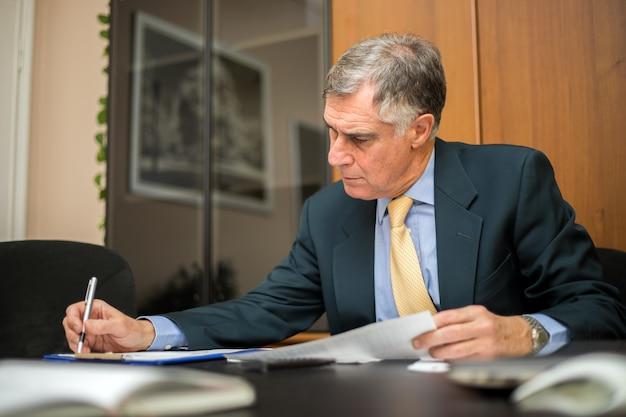 Originais de negócio sênior sérios da leitura do homem de negócios no escritório. gerente sênior revendo cotação de empresa para contrato. Foto Premium