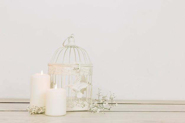 Ornamentos românticos com velas e gaiola Foto gratuita