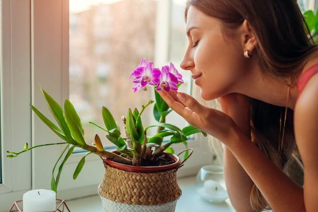 Orquídea de cheiro do dendrobium da mulher no peitoril da janela. dona de casa cuidando de plantas e flores em casa. Foto Premium