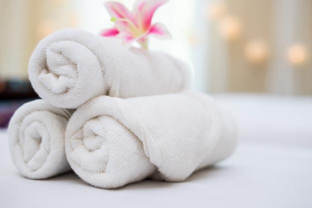 Orquídea rosa bonita na toalha branca no salão de spa. Foto gratuita