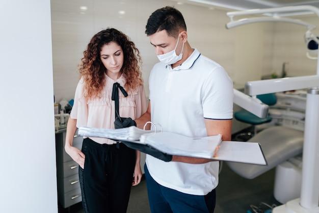Ortodontista e paciente olhando para fichário Foto gratuita