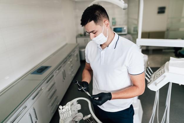 Ortodontista que verifica o equipamento cirúrgico Foto gratuita