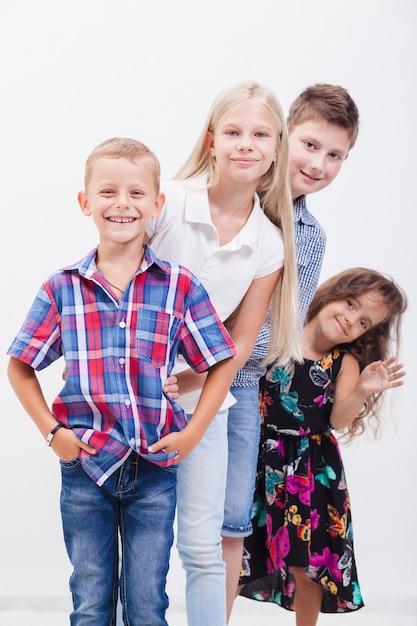 Os adolescentes sorridentes felizes em pé de braços dados sobre fundo branco. Foto gratuita