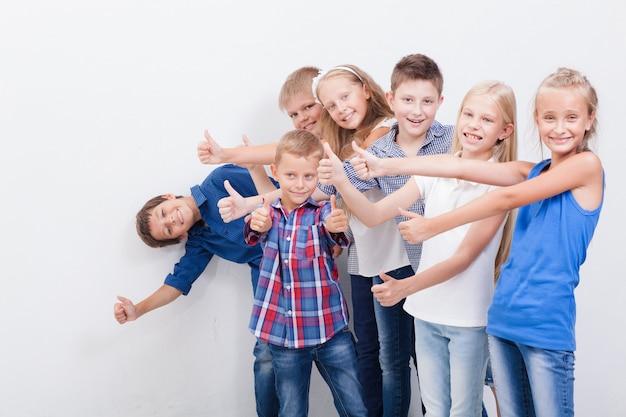 Os adolescentes sorridentes mostrando sinal bem em branco Foto gratuita