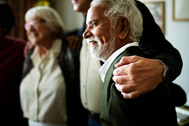 Os adultos idosos se abraçam no ombro um do outro Foto Premium