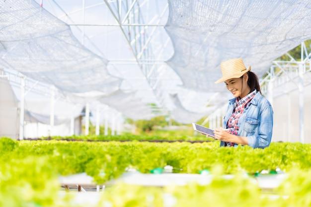 Os agricultores estão registrando dados em tablets na fazenda de salada de vegetais hidropônicos. Foto Premium
