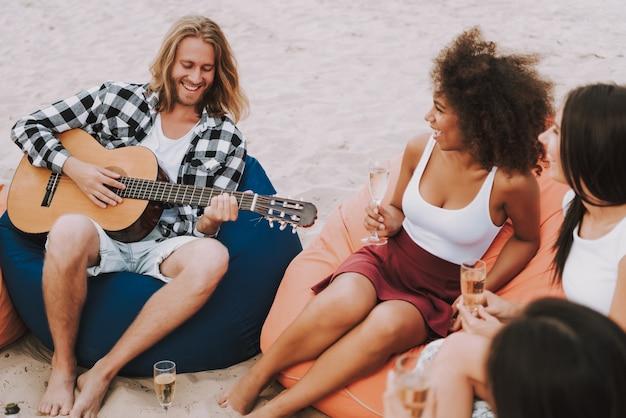 Os amigos apreciam a música que joga a guitarra na praia arenosa. Foto Premium