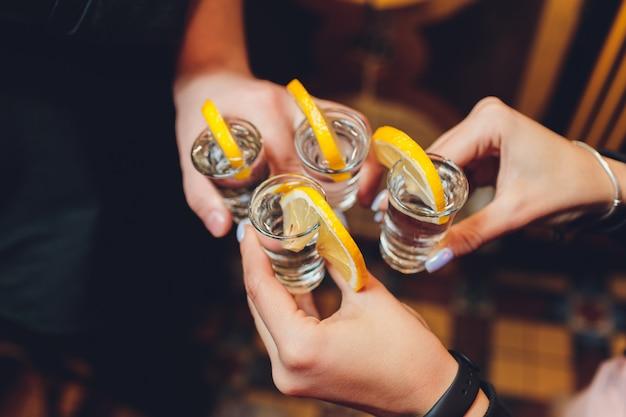 Os amigos que brindam com vidros de tiro acima de uma tabela de madeira velha enegrecem o fundo. Foto Premium
