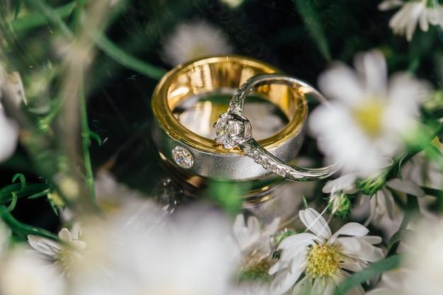 Os anéis de casamento de casal de diamante é colocado no vidro. Foto Premium