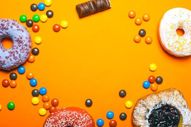 Os anéis de espuma com crosta de gelo colorida e as cerejas do bolo com açúcar pulverizado. doces coloridos do chocolate em uma cópia alaranjada do fundo espaçam a vista superior. Foto Premium