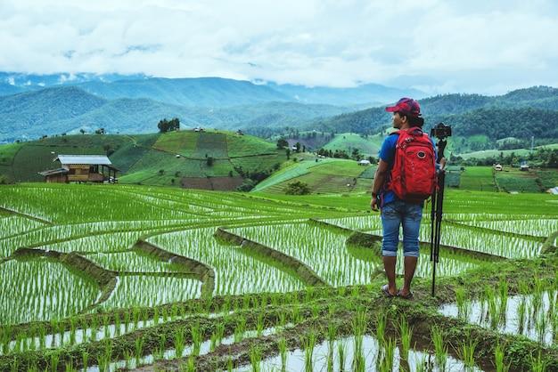 Os asiáticos do homem viajam natureza. viajar relaxar. andar a tirar uma foto no campo. no verão Foto Premium