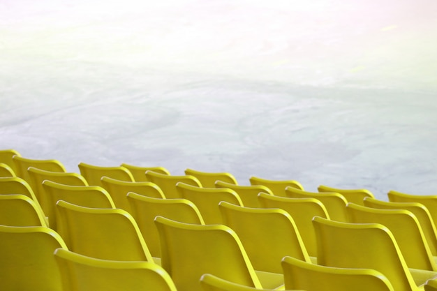 Os assentos amarelos plásticos vazios enfileiram na mostra interna do estádio ou no fundo do lugar do campo de esporte. Foto Premium