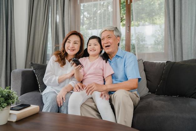 Os avós asiáticos assistem tv com a neta em casa. o chinês sênior, o avô e a avó que usam o tempo da família relaxam com a criança da moça que encontra-se no sofá no conceito da sala de visitas. Foto gratuita