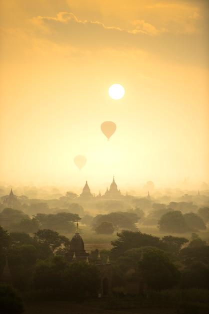 Os balões de ar quente da cena do nascer do sol voam sobre o campo antigo da cidade do pagode em bagan myanmar. Foto Premium