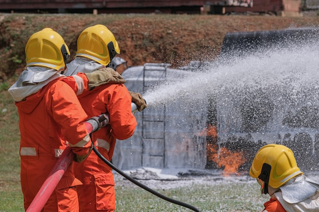 Os bombeiros apagam o fogo com uma espuma química proveniente do carro de bombeiros através de uma mangueira longa. Foto Premium