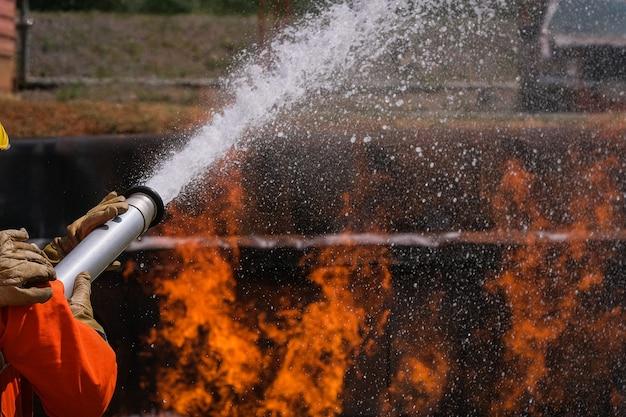 Os bombeiros extinguem o fogo com uma espuma química proveniente do carro de bombeiros através de uma mangueira longa. Foto Premium