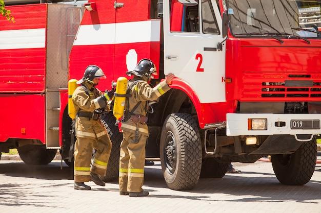 Os bombeiros extinguem um incêndio em um edifício residencial alto. Foto Premium